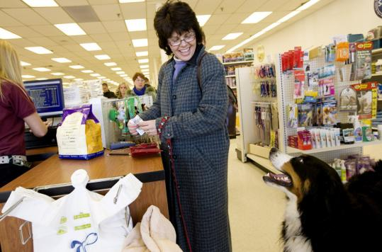 Meg McMahon bought a bag of WellPet food for her dog, Elsa, at Pet Life in Stoneham.