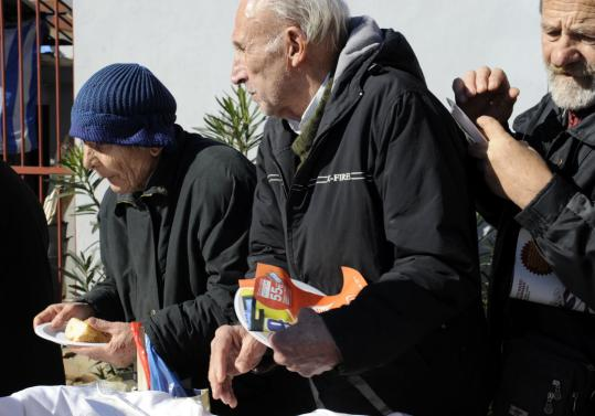 Elderly Greeks waited in line for food being handed out during a Carnival celebration in Athens. Organizers said four times more food was handed out at this year&#8217;s open barbecue.
