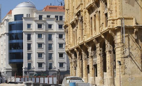 A new elegant building in downtown Beirut (left) stands in contrast with an old bullet-scarred one (right). The capital city is being transformed by a real estate boom.