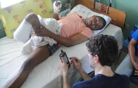 A Global Relief team member relays data about a Haitian man who lost part of a leg.