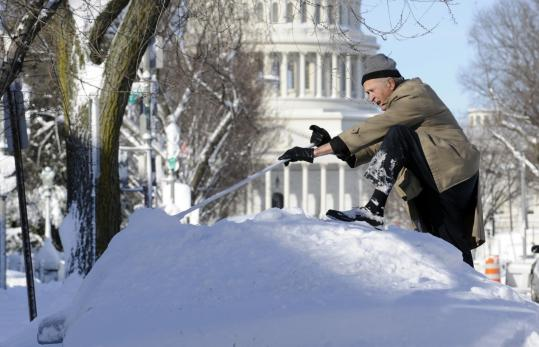 Eugene Wilson used a broom to clear snow off the roof of his car near the Capitol yesterday. Federal agencies will be closed today in Washington, a shutdown that affects about 230,000 government employees who work inside the Beltway.