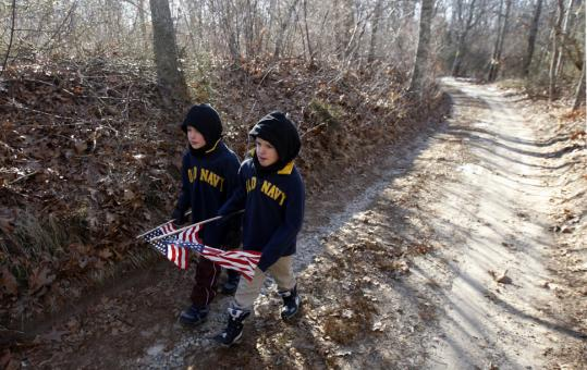 Hunter (left) and Emmett Athearn walked along Rogers Path yesterday as they carried new flags for a veteran's gravesite at a Martha's Vineyard cemetery.