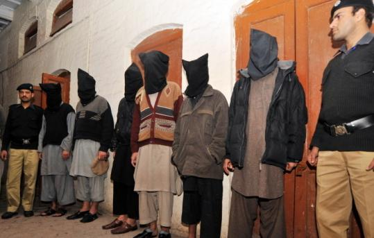 Pakistani police guarded six hooded Taliban suspects after their arrest in an alleged hotel bomb plot yesterday.