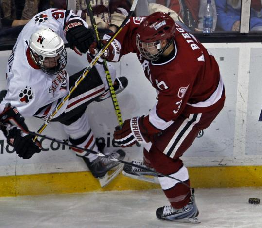 NU's Robbie Vrolyk (left) and Harvard's Alex Biega battle for a loose puck in the second period.