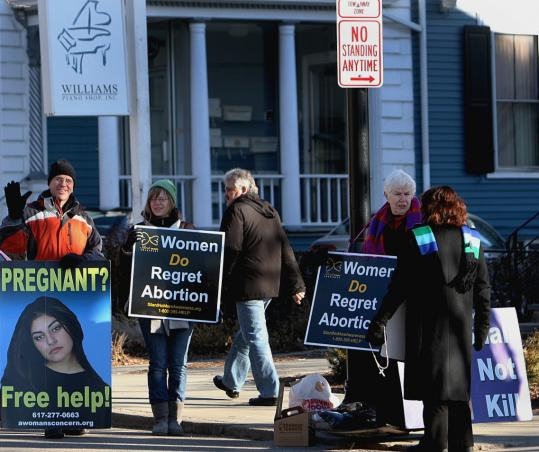 Demonstrators vowed yesterday to picket Women's Health Services in Brookline each day it is open. The opening sparked a lawsuit against the town from nearby residents and businesses.