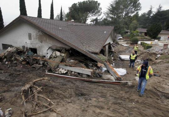 Workers walked past a home yesterday damaged by last weekend's mudslides in La Canada Flintridge, Calif. The National Weather Service has issued a flash flood warning for the area.