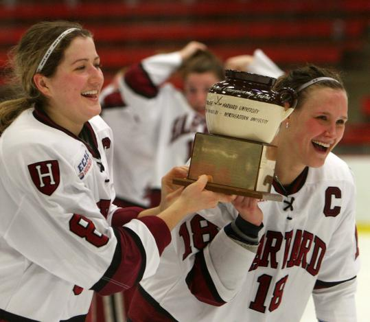 Harvard captains Kathryn Farni (left) and Cori Bassett get one of the first twirls with the Beanpot after the Crimson beat NU.