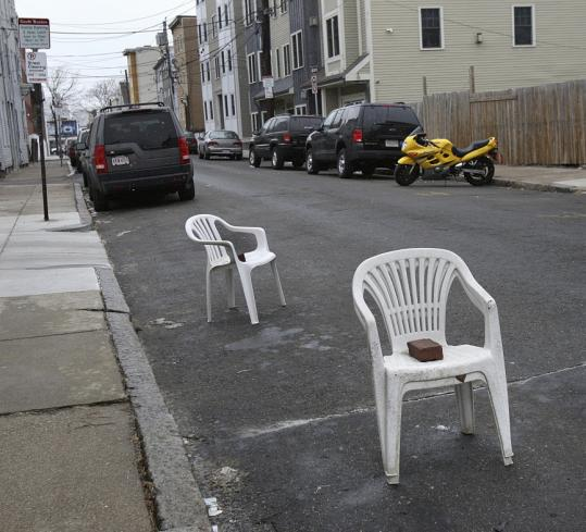 Some residents got a jump on the storm by reserving their spaces before shoveling, as the brick-weighted chairs on West Ninth Street illustrated.