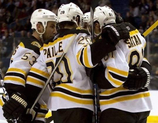 Derek Morris, Daniel Paille, and Miroslav Satan enjoy Satan's first-period goal.