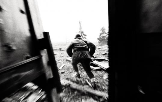 Christopher Morris&#8217;s image of a Chechen fighter fleeing the presidential palace is on exhibit at the Tufts University Art Gallery.