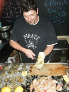Paul Carvallo shucks oysters at the raw bar at Papa Beau's.