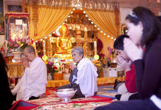 Chi Kong (left) and Vong Choum said a blessing last month before a meal at Lowell's Glory Buddhist Temple.