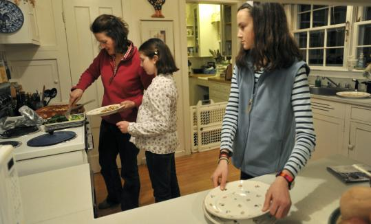 Rebecca Forrester with her daughters Iona (center) and Claudia at their Westford home.