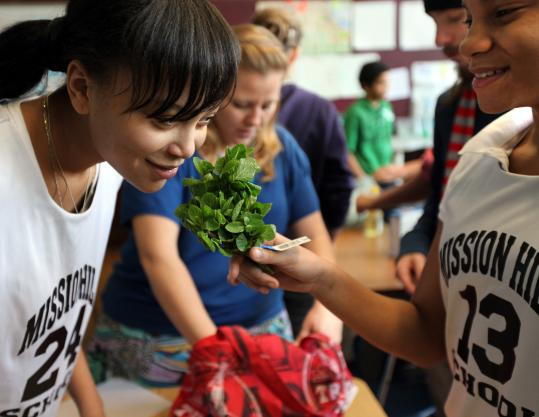 During a Cultural Kitchen project on Lebanon at Mission Hill School, Shayla Scrubb, 14, smells mint held by Sage DelaCruz, 13. The class works in groups to cook tabbouleh, falafel, and tahini.