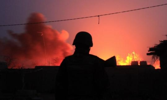 An Afghan soldier stood in front of burning gas tanks set on fire Sunday by Taliban fighters in Marja, where troops say they are fighting with a handicap due to strict rules of engagement.