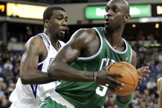 Celtics forward Kevin Garnett (9 points, 9 rebounds) puts a baseline move on Sacramento defender Donte Greene.