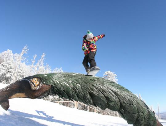 The Stash, an all-natural terrain park, features wooden fences, logs, and a masoned stone ledge.