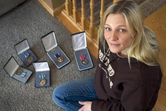 Staff Sergeant Katie Blackwell of Minnesota, seen with medals she was awarded, estimated she and her husband, also a soldier, together are owed $8,000 in post-deployment paid time off.