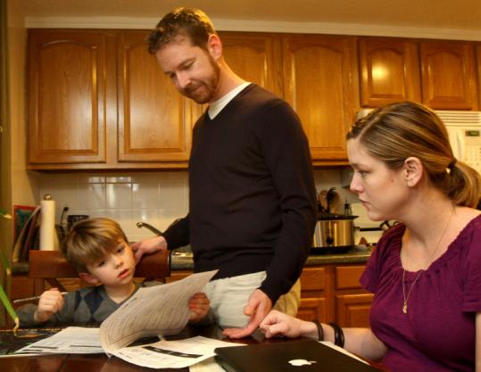 Derek and Lisa Evans helped their 6-year-old son, Owen, with some schoolwork at the family's home in Brookline.