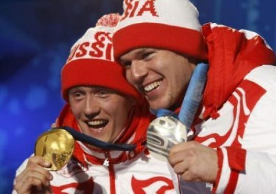Cross-country skiing gold medallist Nikita Kriukov of Russia celebrates with compatriot and silver medallist Alexander Panzhinskiy.