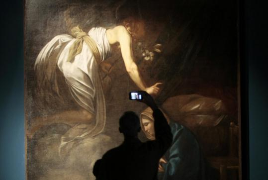 """A man photographs """"Anunciation'' yesterday at the Scuderie del Quirinale in Rome. The museum's Caravaggio exhibit opens today."""