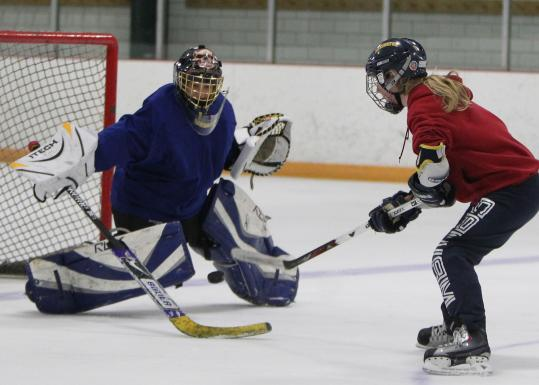 Lexington High senior goalie Nina Riley, with 34 careers shutouts to her credit, stops teammate Carolyn Avery's shot during practice at the Hayden Ice Rink.