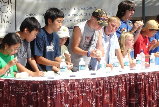 Participants in an onion-eating contest show their mettle at the Maui Onion Festival.