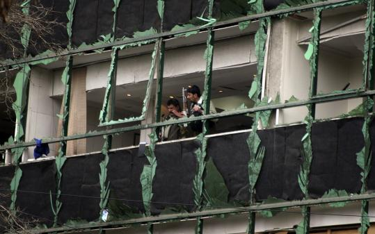 Afghan security forces kept watch from a damaged building in Kabul after insurgent attacks yesterday.