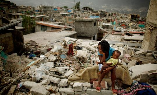 Sherider Anilus, 28, and her daughter, 9-month-old Monica, traveled yesterday to the spot in Port-au-Prince where her home collapsed in the earthquake.