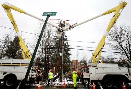 Crews worked to restore electric service in Bow, N.H., yesterday. A large pine tree that snapped at its base during a windstorm earlier in the week had brought down wires. Some residents in the state could remain without power for several days.