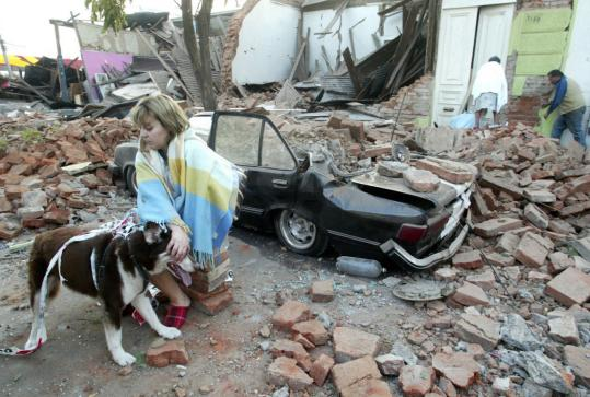 A woman sat in front of a quake-damaged house in Talca, Chile. At right, vehicles were scattered along a highway that collapsed near Santiago.
