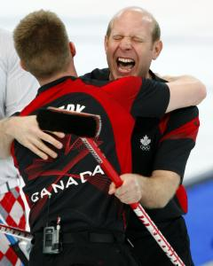 """Kevin """"Old Bear'' Martin (right) gets a big old bear hug from John Morris after Canada beat Norway to clinch the gold. The dominating Canadians went 11-0 in the tournament."""