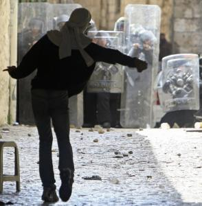 A Palestinian threw a stone toward the shields of Israeli riot police in Jerusalem's Old City yesterday.