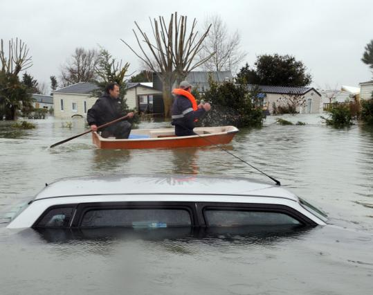 Two residents of Aytre, France, paddled a dinghy yesterday around the flooded town. At least 62 people across Western Europe were killed by the devastating storm, called Xynthia.