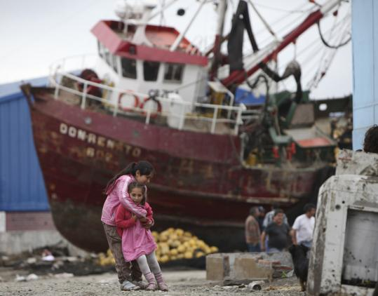 Girls played near a boat sitting in the middle of a street in Talcahuano, Chile, 10 days after the 8.8-magnitude earthquake struck. Chileans were shocked by the looting that followed.