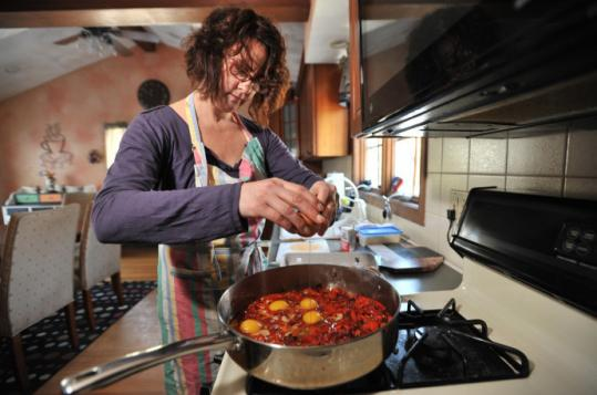 For her roasted-pepper frittata, Joy Cagno breaks eggs into the pan, folding and stirring them into the peppers.