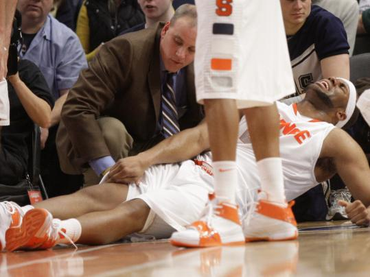 Syracuse starting center Arinze Onuaku gets tended to by trainers after injuring his right knee.