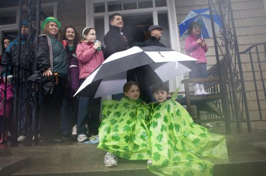 Lauren George, 7, of Dorchester, and Jack Kenneally, 5, of South Boston huddled under an umbrella to watch the Saint Patrick's Day parade in South Boston.
