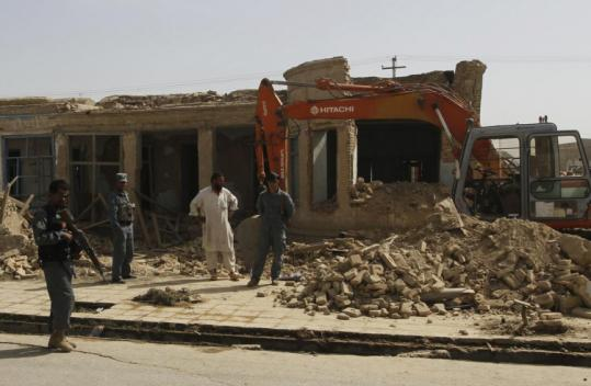 Afghan police stood near a house damaged in an explosion outside police headquarters in Kandahar yesterday.