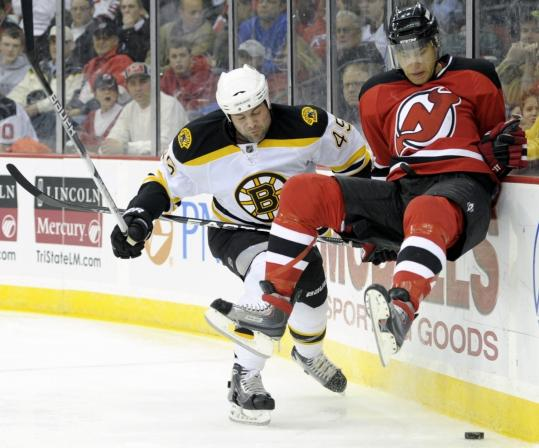 Bruins defenseman Mark Stuart bumps Dainius Zubrus off the puck — and the ice — with a hard check in the second period.