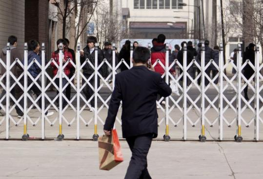 A gate crosses an entrance of the Lanxiang Vocational School in Jinan, China. Reports have tied the school to online attacks on Google e-mail accounts and on about 20 other firms.