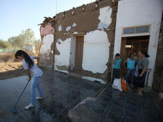 A woman swept the floor of her home in Retiro, Chile, on Monday. The quake caused nearly $30 billion in damage.