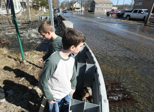 Alex Spano, 7, and his brother, Joseph, 10, behind him, checked out the overflow from the Monatiquot River that ran onto Adams Street in Braintree yesterday.