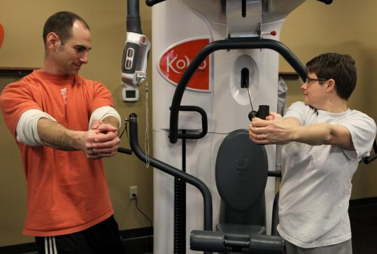 Paul Romeo, who works at the Koko FitClub in Needham, demonstrated a trunk rotation exercise to Teresa Combs on the Koko Smartrainer last week. It is one of two Koko gyms in Massachusetts.