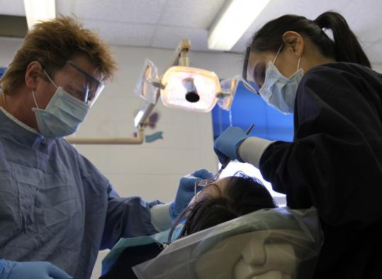Assisted by Susan Clifford (left), Dr. Marie Bugayong cleaned the teeth of a mentally disabled patient last week in the Tufts Dental Facility at Fernald Development Center in Waltham, which will be closing in June.