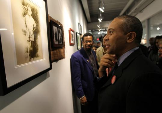 Governor Deval Patrick admires photographs from his father's collection at the Berklee College