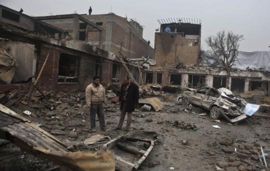 People stood in the compound of a damaged guesthouse in Kabul, the day after suicide attacks in February. There were 26 attempted attacks using improvised explosives in Kabul last year.