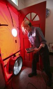 Roseann Mitchell of the Community Action Agency checked airflow readings as part of a blower door assessment in San Francisco.
