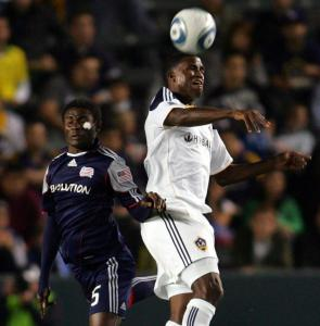 Edson Buddle of the Galaxy (right) wins a high ball against the Revolution&#8217;s Emmanuel Osei.