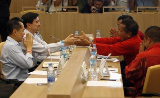 In a gesture of civility, Prime Minister Abhisit Vejjajiva (left) shook hands with Veera Musikapong, leader of a prodemocracy movement, at yesterday's meeting in Bangkok.